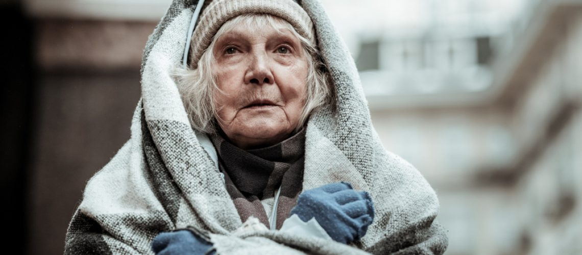 Feeling,Cold.,Portrait,Of,A,Cheerless,Aged,Woman,While,Feeling