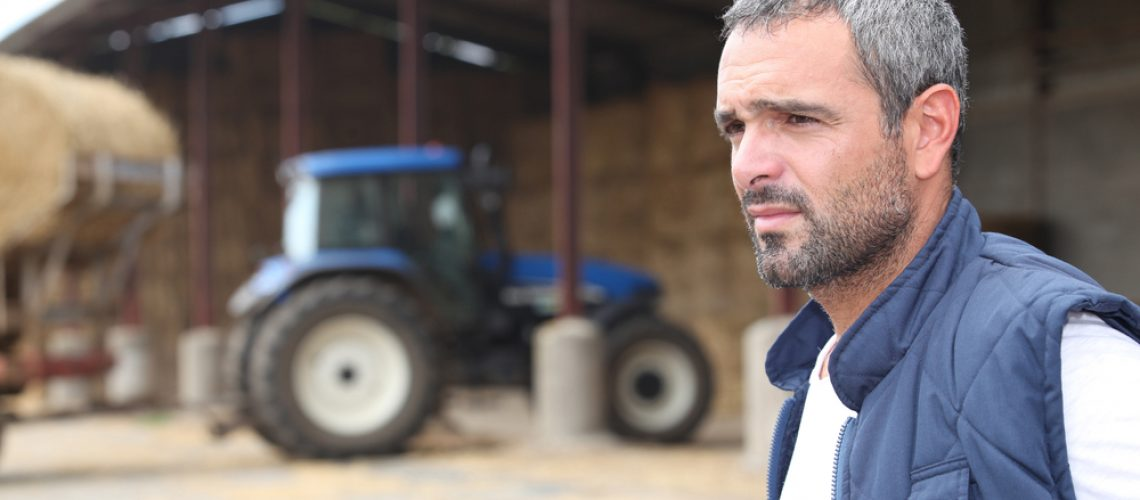 Farmer,Standing,In,Front,Of,A,Barn,Containing,A,Tractor